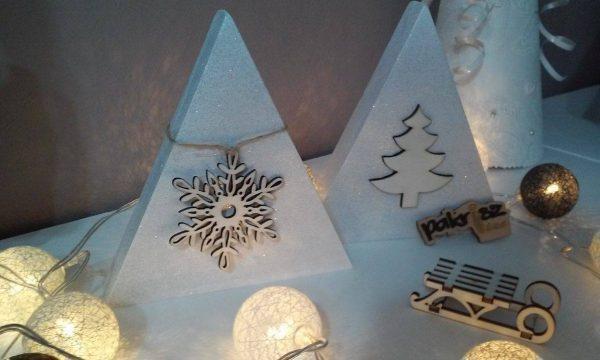 Dekorácia s vianočnou ozdobou. Biela farba. Vianočná ozdoba vločka a ihličnatý stromček